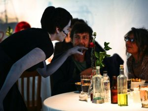 Performaers interacting with audience members at dinner performance event by Interm3dia Students