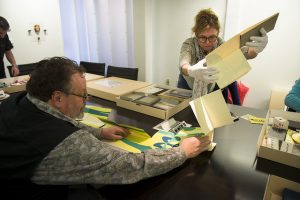 Students and faculty study looking at artist's books
