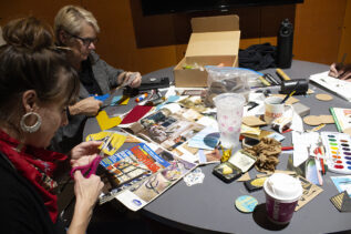 Students wrokiing on cut and paste project at a table in the IMRC Center