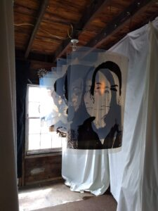 Seven portrait photographs of women printed on translucent acetate hang from the ceiling. The portraits are three feet long by two feet wide. Each portrait hangs eight inches directly in front of the other, aligned in front of a window.