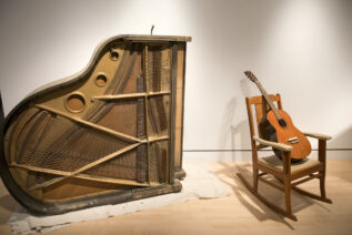 Image of Guitar on chair and piano on it side as part of a student project exploring experiment music and sculpture
